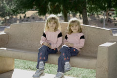 Double Cute. Twins Sitting On Park Bench Royalty Free Stock Photos