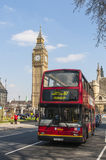 Double-decker bus driving by Big Ben. LONDON, UK - APRIL 02: Famous red double-decker bus driving by Houses of Parliament, with Big Ben prominent in the picture Stock Photography