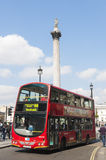 Double-decker bus driving by Trafalgar Square Stock Images