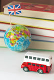 Double-decker bus, globe and flag of Great Britain on a pile of books background. Royalty Free Stock Image