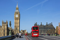 Double-decker bus. LONDON, UK - APRIL 12, 2015: double-decker bus passes pedestrians walking in front of Big Ben and Houses of Parliament on Westminster Bridge Royalty Free Stock Photo