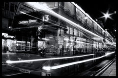 Double decker bus at night Oxford Street with light trails. London, UK – Oct 6, 2011: Black & white image of a No 13 red double decker bus at night passing Royalty Free Stock Image
