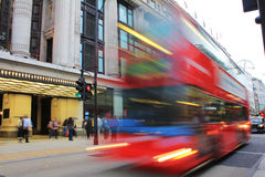 Double Decker Bus outside Selfridges in London. A Double Decker Bus whizzes past the camera outside Selfridges on Oxford Street in London, UK Royalty Free Stock Image