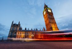 Double-decker bus passes pedestrians walking in front of Big Ben and Houses of Parliament Royalty Free Stock Photos