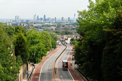 Double-decker bus on a road with London skyline in the background. Red double-decker bus on a road with London's famous buildings skyline in the background Stock Photos