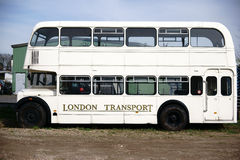 Double decker bus on scrap yard. The side view of an old discarded double decker bus on a scrap yard Stock Photo