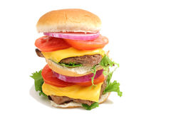 Double decker cheeseburger on white. Shot of double decker cheeseburger on white stock images