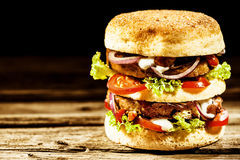 Double-decker or club freekeh burger with trimmings. Double-decker, or club, freekeh burger with assorted fresh salad trimmings on a golden bread roll served on Royalty Free Stock Photos