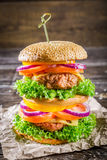 Double-decker homemade burger made from fresh vegetables. On old wooden table Stock Image