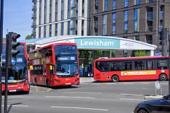 Double Decker and Single Decker Buses Driving Past Lewisham DLR Station royalty free stock photos