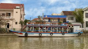 Double decker tour boat anchored along shore Thu Bon River, Hoi An. Pictured is a wooden double decker tour boat anchored along the shore of Thu Bon River, Hoi royalty free stock images