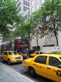 A double-decker tour bus and yellow cabs in New York City Royalty Free Stock Photos