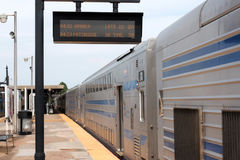 Double Decker train on Babylon Platform with sign showing LATE. Babylon, N.Y. USA - 29 June 2017: Double Decker train sitting on the Babylon platform has to wait Royalty Free Stock Image