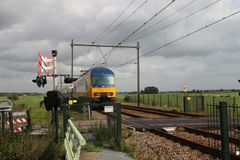 Double decker train at railway crossing in Moordrecht. Double decker train local commuter at railway crossing in Moordrecht in the Netherlands Stock Image
