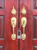 Double door handle. Double door handle, classic style, gold color on wooden door and padlock stock image