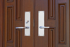 Double door handles on mahogany. Double chrome door handles on twin mahogany doors in foyer Royalty Free Stock Photo