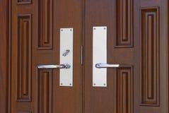 Double door handles on mahogany. Double chrome door handles on twin mahogany doors in foyer royalty free stock photo