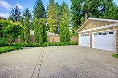 Double doors garage with wide, long driveway. North America. Double doors garage with wide, long driveway and lots of greenery. North America Stock Photography