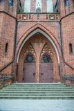 Double doors of the main entrance. Garrison Church in Olsztyn, Poland. Double lancet doors of the main entrance. Garrison Church of Our Lady Queen of Polish in royalty free stock photography
