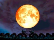 double dragen sur le ciel nocturne de lune de plein sang de toit Images libres de droits