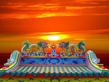 Double dragon on chinese temple roof and sunset Stock Photo