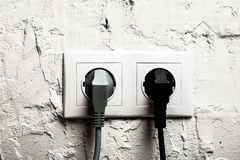 Double electrical socket with plugged cables. On brick wall Royalty Free Stock Photos
