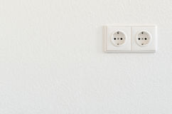 Double electrical socket on white wallpaper. Two electrical sockets symbolizing connectivity, clean energy and power Stock Photos
