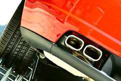 Double exhaust and wheel of a sports car. Powerful double exhaust and the left rear wheel of a red sports car in showroom Royalty Free Stock Photography