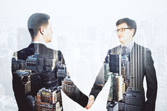 Double explosure with businessmen shake hands and financial city Stock Images