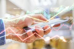 Double explosure with man hand holds smartphone and business cha Stock Photo