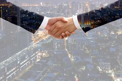 Double exposition d'accord de poignée de main d'homme d'affaires avec le citysca images stock