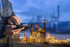 Double exposition d'homme d'affaires vérifiant l'usine d'industrie de raffinerie de pétrole photo stock