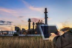 Double exposition d'homme d'affaires vérifiant l'usine d'industrie de raffinerie de pétrole par le comprimé pendant la nuit comme photographie stock