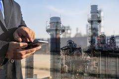 Double exposition d'homme d'affaires vérifiant l'usine d'industrie de raffinerie de pétrole par le téléphone intelligent photographie stock libre de droits