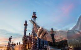 Double exposition d'homme d'affaires vérifiant l'usine d'industrie de raffinerie de pétrole par le téléphone intelligent pendant  image libre de droits
