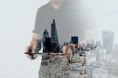 Double exposition d'homme d'affaires de succès utilisant le comprimé numérique Image stock