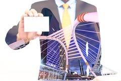 Double exposition d'homme d'affaires tenant ou montrant la carte de visite professionnelle de visite et le fond vides de ville Photo stock