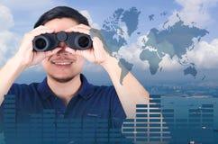 Double exposition d'investisseur asiatique avec des jumelles Au-dessus de la vue de paysage marin de l'antenne Photographie stock libre de droits