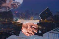 Double exposition d'une poignée de main d'homme d'affaires sur la vue aérienne du C.A. Images libres de droits