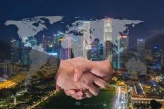 Double exposition d'une poignée de main d'homme d'affaires sur le monde Carto global Images libres de droits