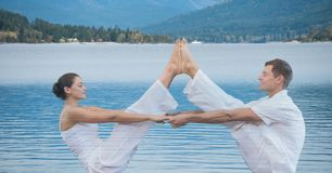 Double exposition de l'homme et de la femme exécutant le yoga s'exerçant au-dessus du lac Photographie stock