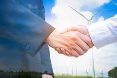 Double exposition de poignée de main avec la turbine de vent Concept d'écologie Images stock