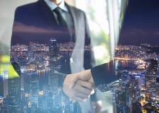 Double exposition de poignée de main et de ville, de poignée de main d'affaires et de gens d'affaires photos stock
