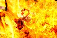 Double exposition de pompier tenant le bec à haute pression de tuyau d'incendie avec la flamme du feu de flamme Photos stock