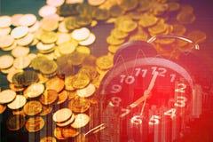 Double exposition des piles de réveil et de pièces de monnaie avec le fond de ville et le graphique de finances, heure pour le co photo stock