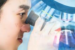 Double exposition Jeune scientifique regardant le microscope dans la La Photo libre de droits