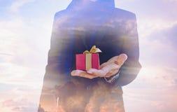 Double exposition, ton de vintage, homme d'affaires avec le boîte-cadeau en main, et beau ciel d'imagination Photographie stock