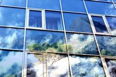 Double exposition Windows d'un bâtiment avec les nuages et la nature réfléchis, montagne, mer Photos libres de droits