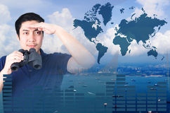 Double exposure of Asian investor with binoculars. Over seascape view from aerial and financial graph Stock Images