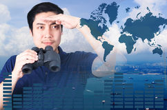 Double exposure of Asian investor with binoculars. Over seascape view from aerial and financial graph stock photography